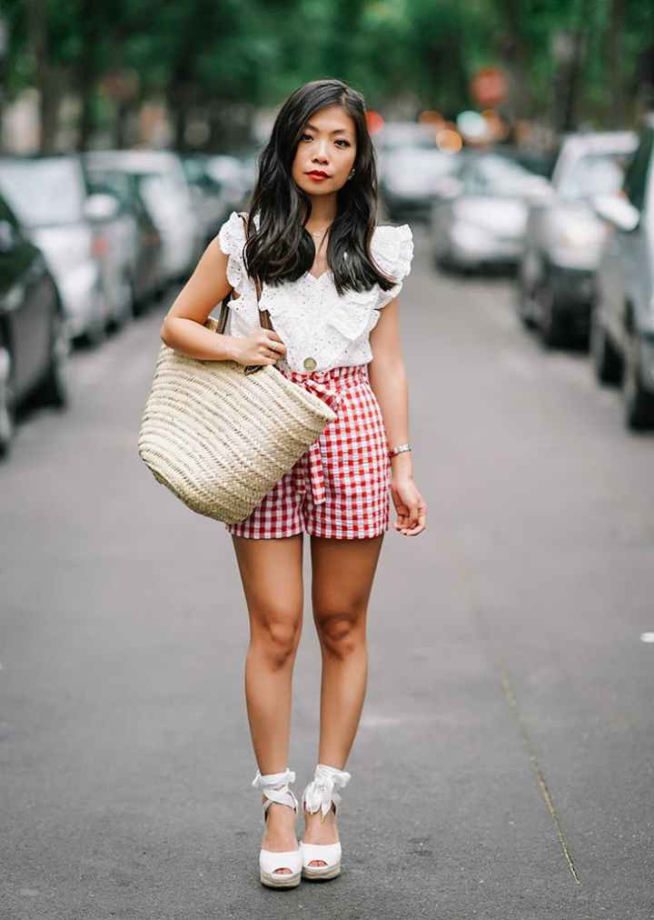 woman-wearing-a-white-top-and-red-gingham-shorts